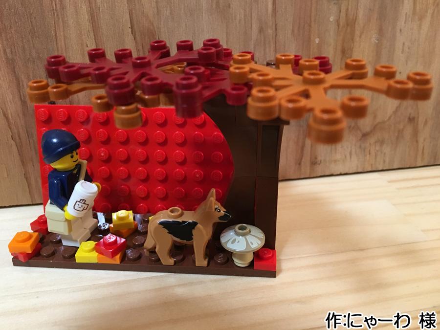小さなプレートの上に作られた紅葉を散歩する犬と飼い主のレゴ作品2枚目